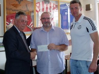 Rupert Hill of Heath Big Local presents a cheque of £23000 to Graham Shenton and Martin Gadsby of Uttoxeter Town Football Club