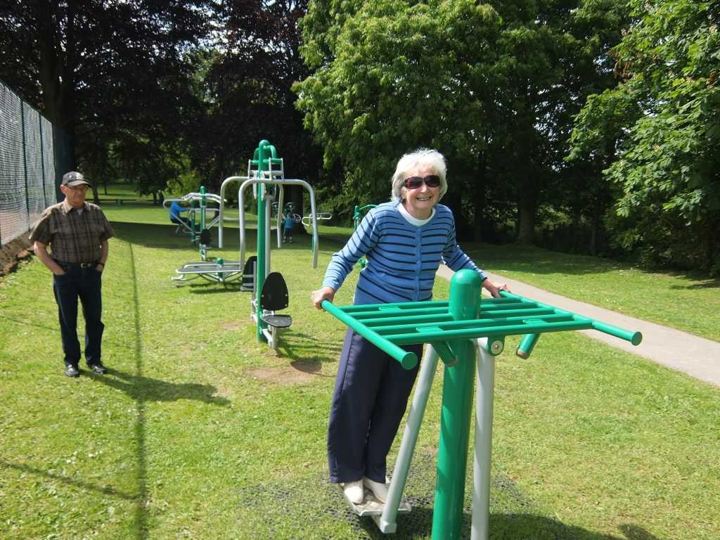 Sheila Gratton on a piece of gym equipment at Bramshall Park with Colin Gratton looking on